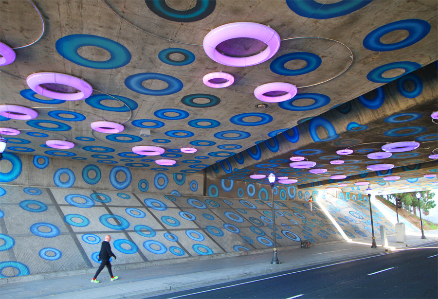 Sensing YOU is an interactive artwork utilizing light and paint to define a major downtown gateway in San Jose CA. The installation is defined by over 1000 painted circles and 81 individually controlled illuminated rings that play a variety of patterns and low-resolution mapped video over the ceiling surface of the I-87 highway underpass. The patterns are activated by pedestrians and bicyclists moving through the space- setting off pre-programmed sequences.