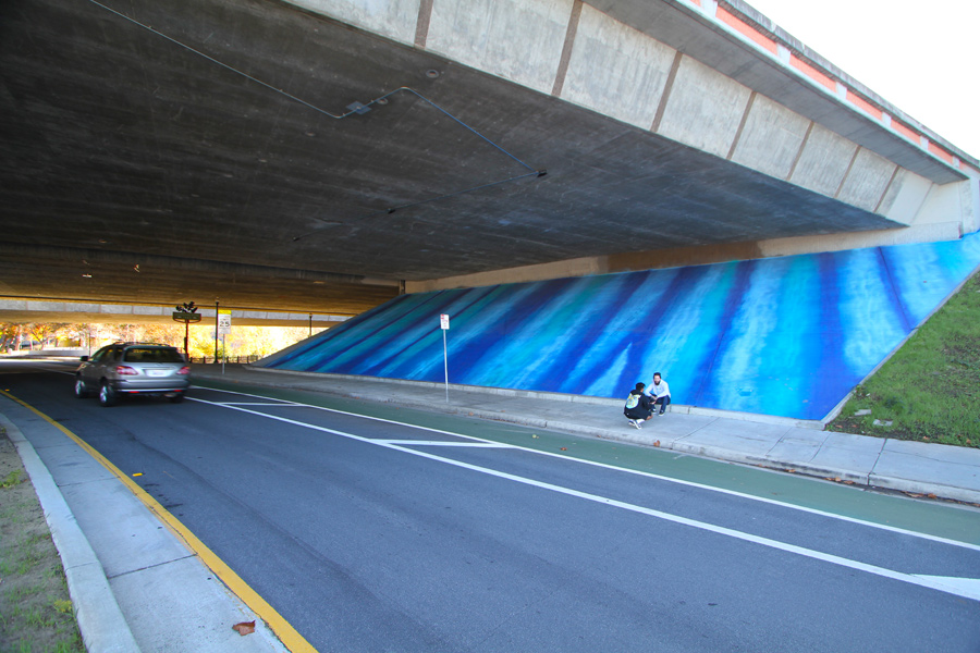 Sensing WATER is a weather-responding and interactive artwork utilizing light and paint to define a major downtown gateway in San Jose CA. The project is composed of 2 elements, the massive painted sloped wall that abstractly references flowing water, and the overhead evening lighting that illuminates with rippling patterns of light the underpass of I-87. The project uses real-time NOAA weather data to compose different patterns of light on the ceiling. (e.g.: 0-5mph winds vs thunderstorms). The projected light maintains a similar palate to the painted sloped wall, yet becomes dynamic depending on the weather.